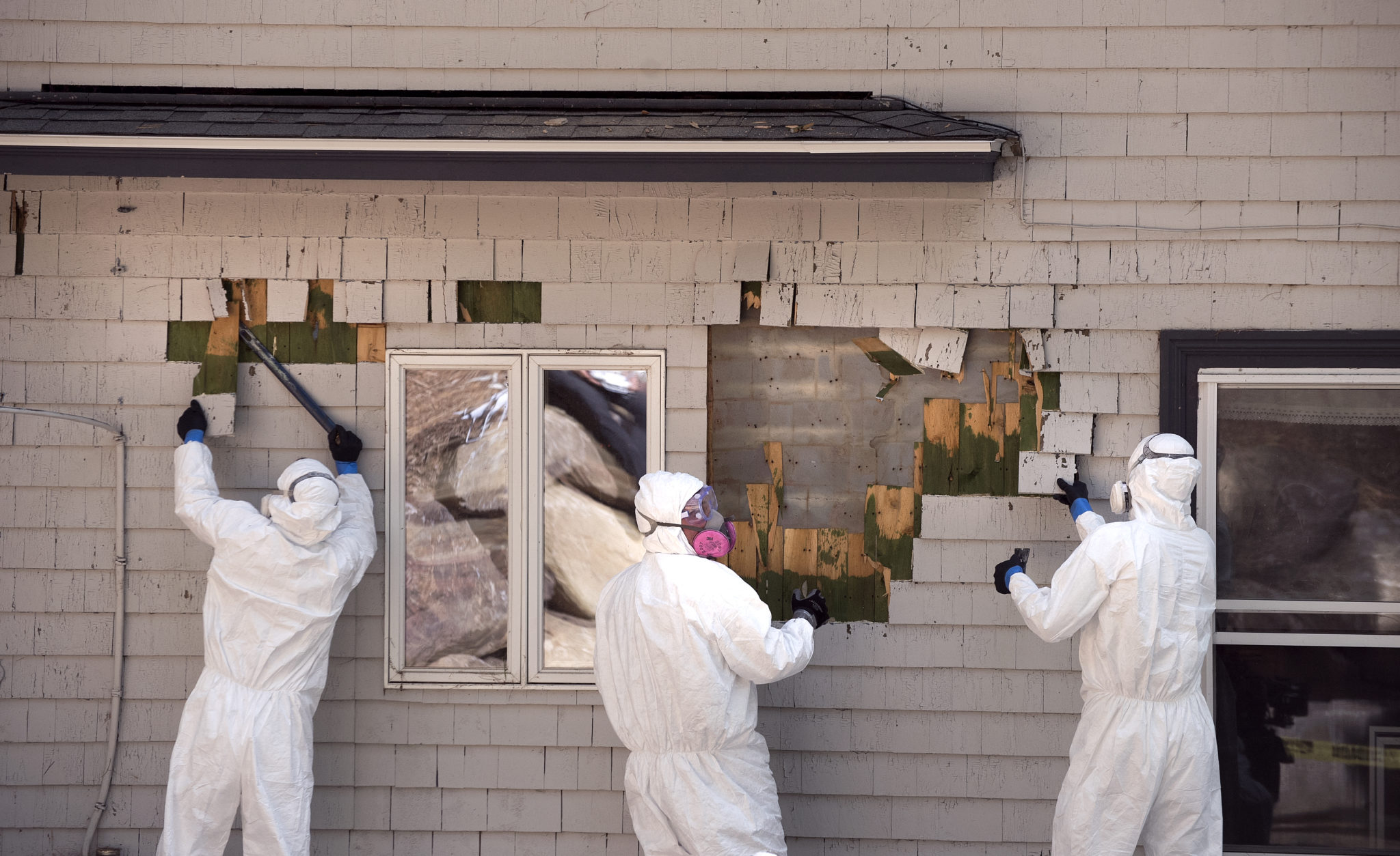 Workers remove cedar shingles, coated with lead-based paint from Jon and Briar Fishman's camp in Northport, Maine, where lead hazards sickened their child. | Gabor Degre