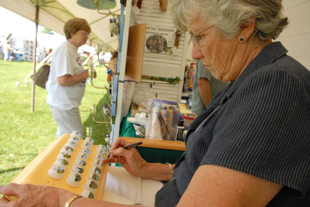 Beth Fewell, co-owner of Coastal Designs in Maine, paints miniature coastal scenes on night lights in her booth at the United Maine Craftsmen second annual Bangor Waterfront Arts & Crafts show.