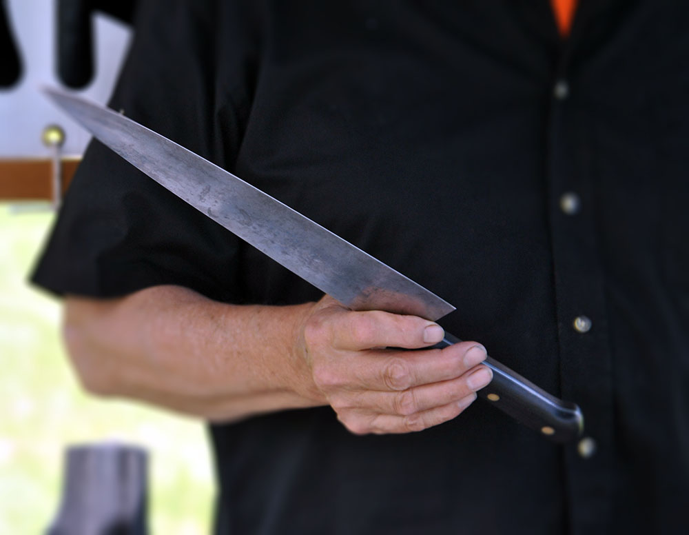 Neill Peterson, owner of ACE Sharpening and Window Cleaning in Belfast, Maine, holding a carbon steel knife.
