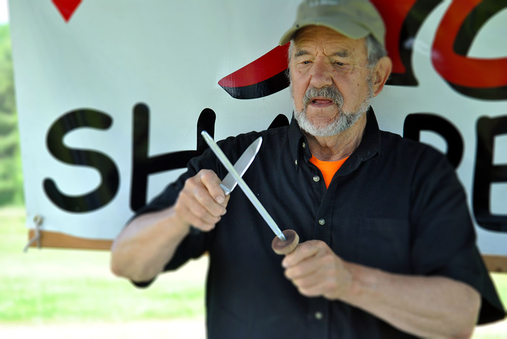 Neill Peterson, owner of ACE Sharpening and Window Cleaning in Belfast, Maine, demonstrates how to care for kitchen knives at the Maine Organic Farmers and Gardeners Association's annual Farm and Homestead Day in 2019.