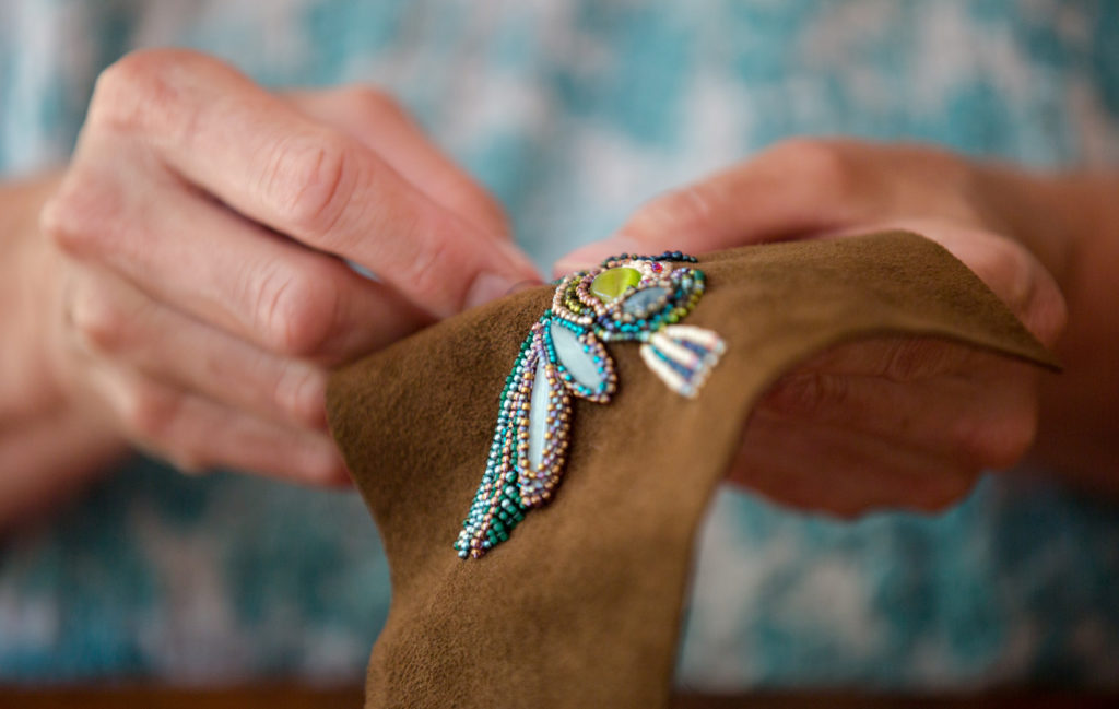 Leslie Jones embroiders beads into a hummingbird pattern at her home in Southwest Harbor, Maine. If trying to discover crafts that make money, it may be helpful to hone in on a specialty, like embroidering specific types of beads into nature scenes. You can then perfect that craft, plus your work becomes recognizable to customers.