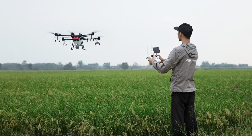A man operates a drone in a field.