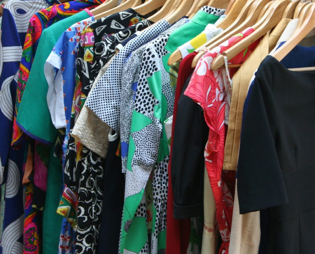 A close shot of a shirts and dresses hanging in a closet.