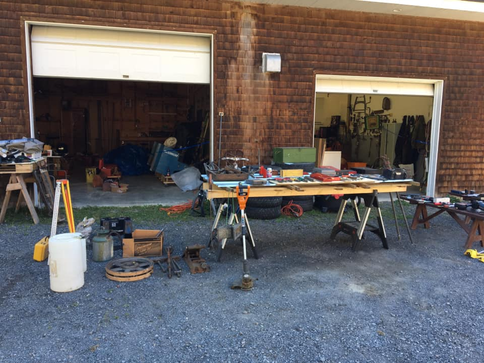Tools and related gear set up on tables in front of a large garage with open bay doors.