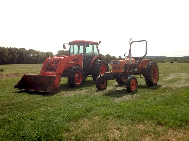 Two red tractors parked next to each other in a field. One with an enclosed cab and the other with a rollover protection system.