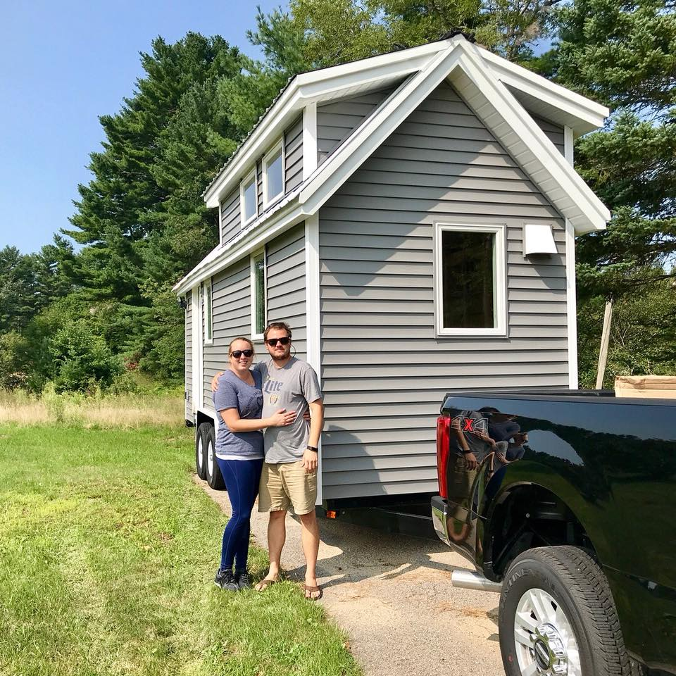 A couple stands in front of their tiny house.