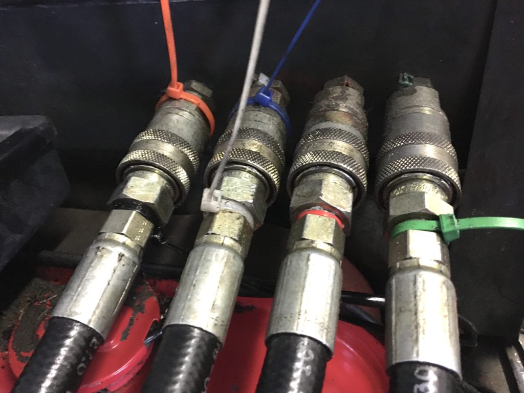 Four hydraulic lines connected to a tractor.