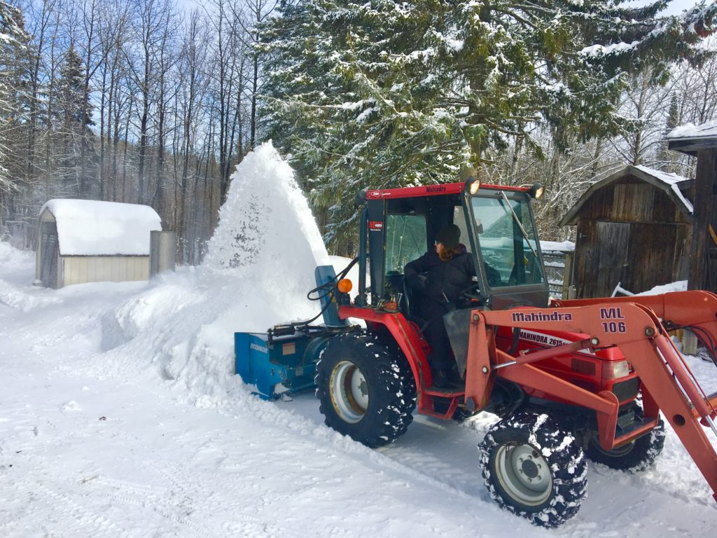 A red tractor with a blue rear-mounted snowblower blowing snow.
