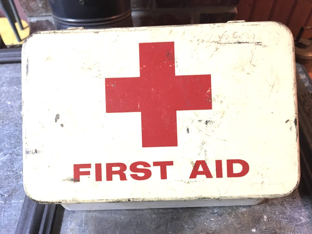 A metal first aid box with a giant red cross on it.