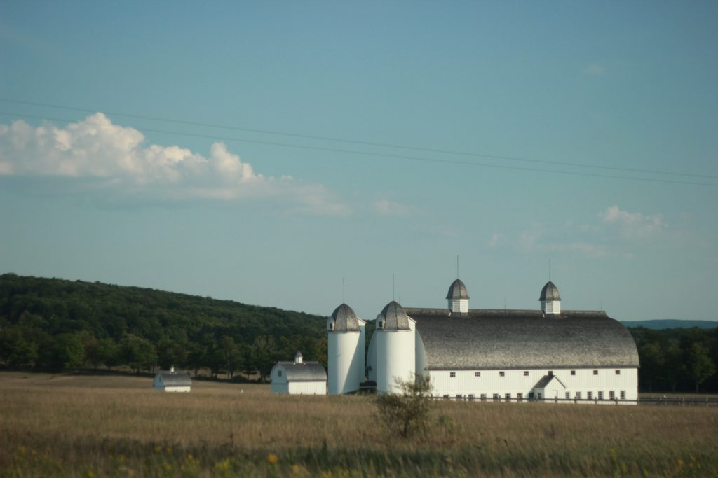 A large white barn with two grain silos.