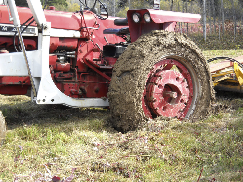 A large farm tractor stuck in the mud.