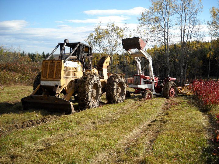 A farm tractor being pulled from the mud by a large, yellow skidder.