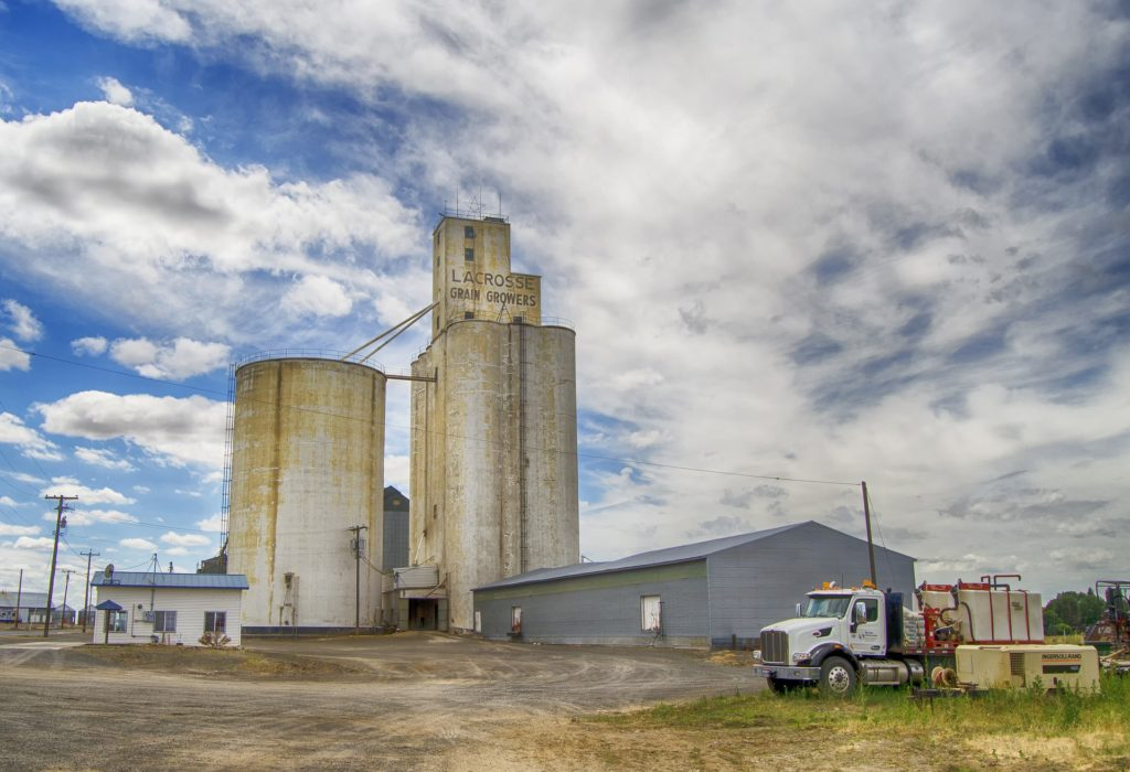 A grain elevator behind a metal shed and a white building.