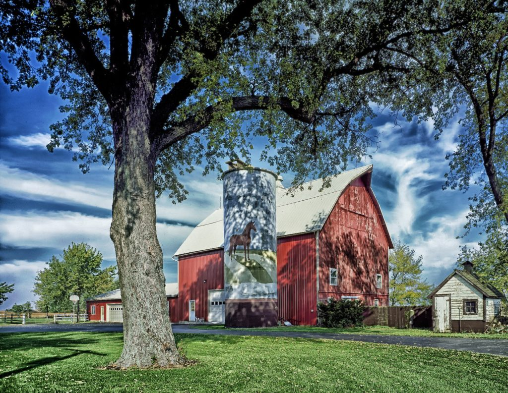 A tall red barn with a grain silo that has a horse painted on its side.