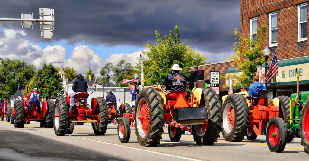 A parade of antique, red tractors.