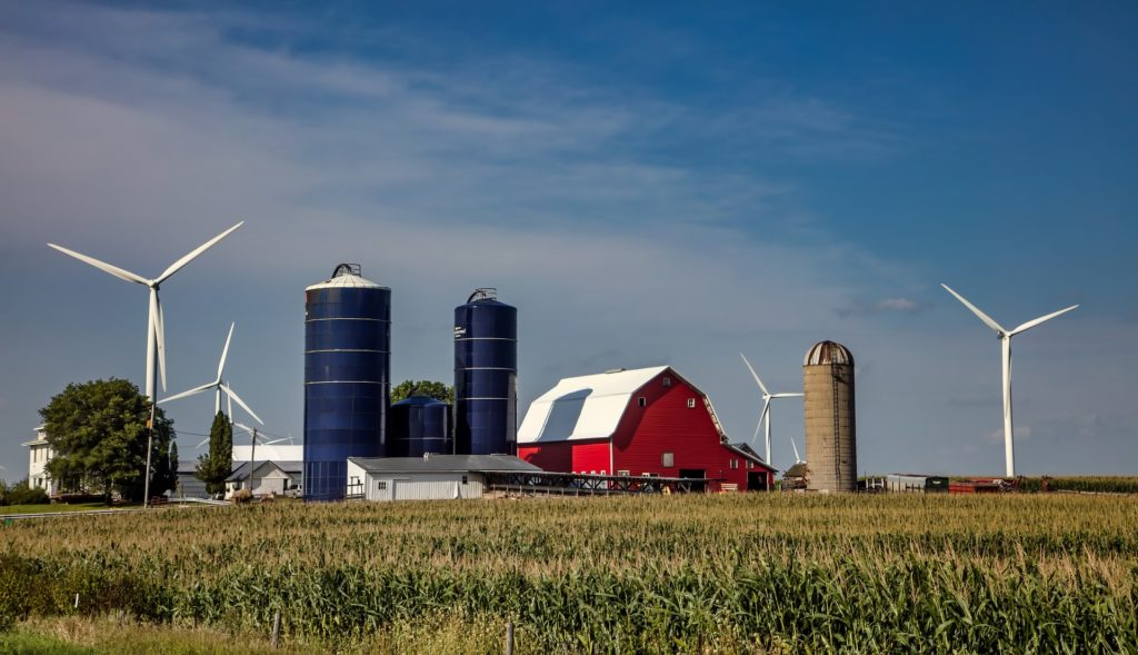 A red barn with three grain silos and four large power-generating wind turbines.