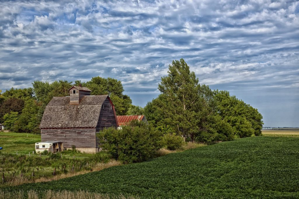 An old barn next to trees and a green field under a cloudy sky.