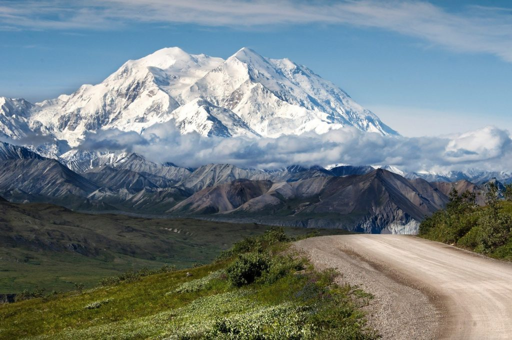 A dirt road with a tall, snow capped mountain.