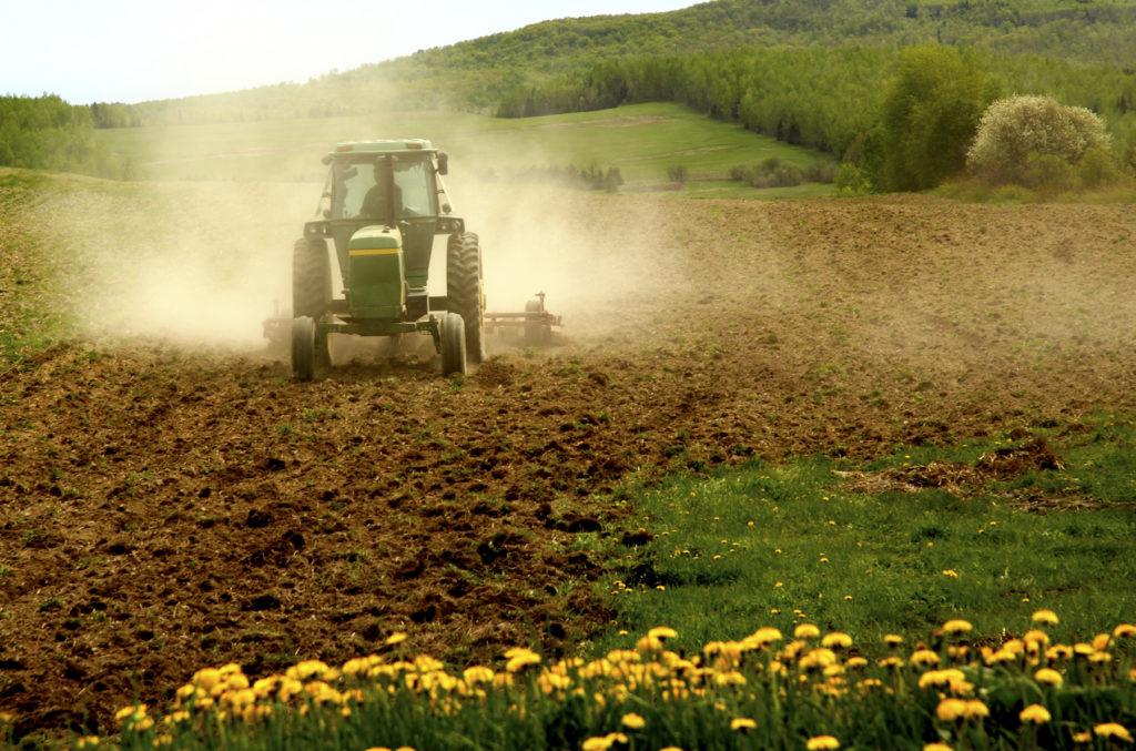 A John Deere tractor pulling tiller over a dusty field.