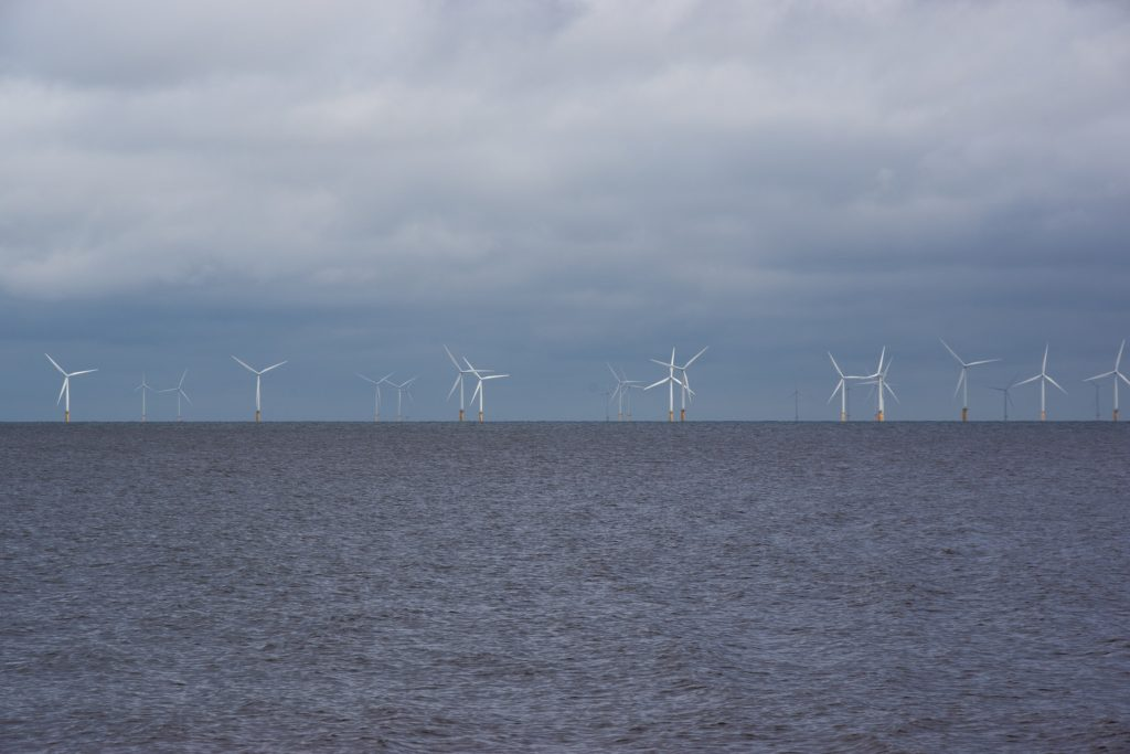 A row of large wind turbines set offshore in the ocean.